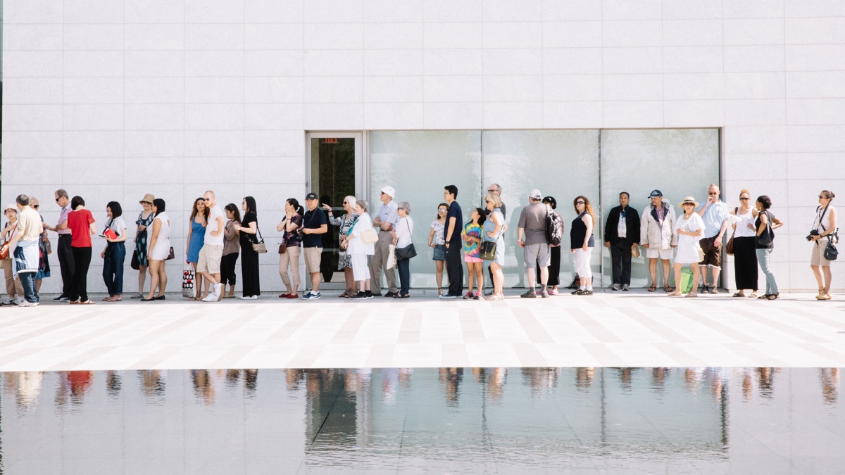 Forty people stand in line outside the Aga Khan Museum on a sunny summer day, with their reflections visible in a pool in the foreground.