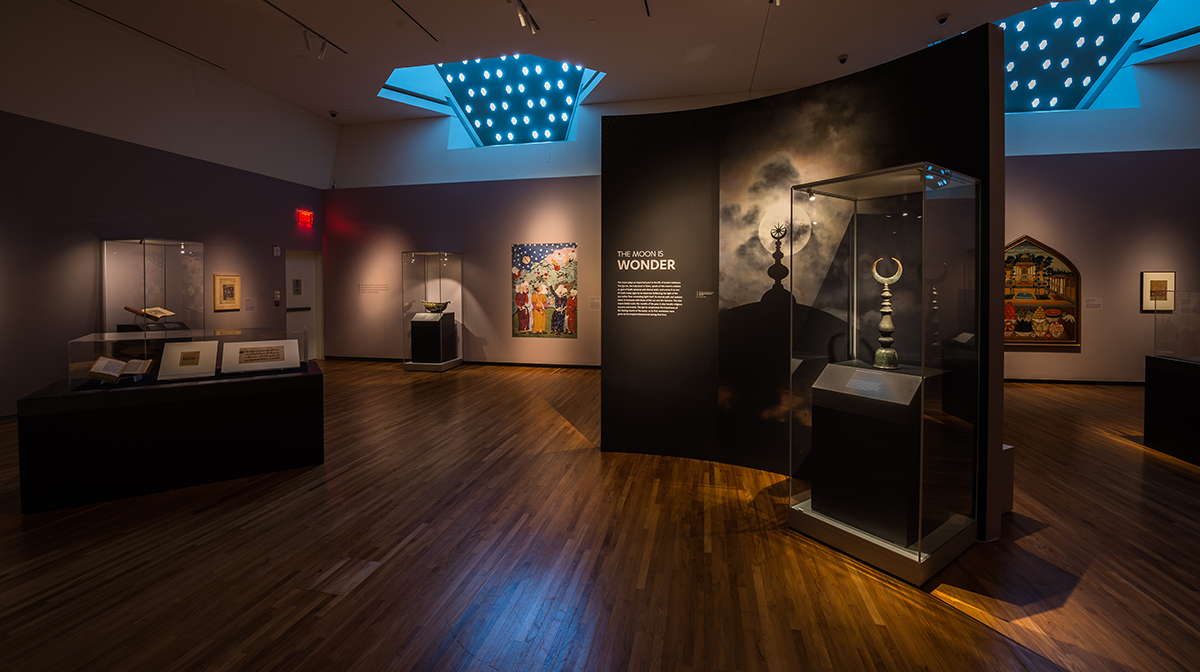 f12159af0c ... An exhibition space with artifacts displayed on shelves and images on  the wall.