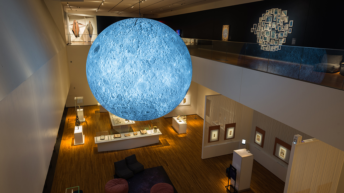 A three-dimensional sculpture of the moon, featuring details from NASA imagery of the lunar surface, hangs over the Aga Khan Museum's first-floor gallery.