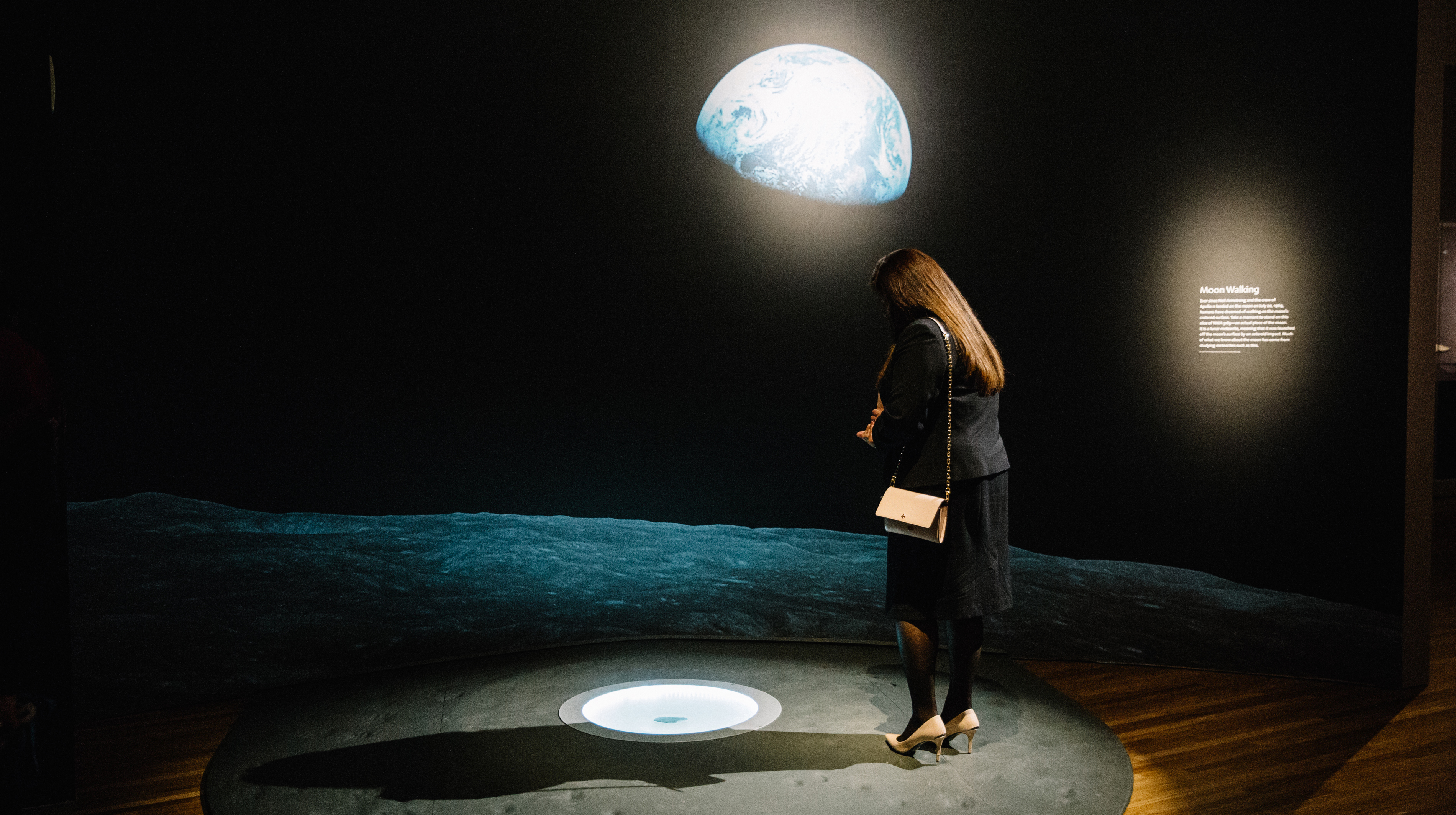 2db9437b55 ... A woman looking down at the floor with an image of the earth on the wall