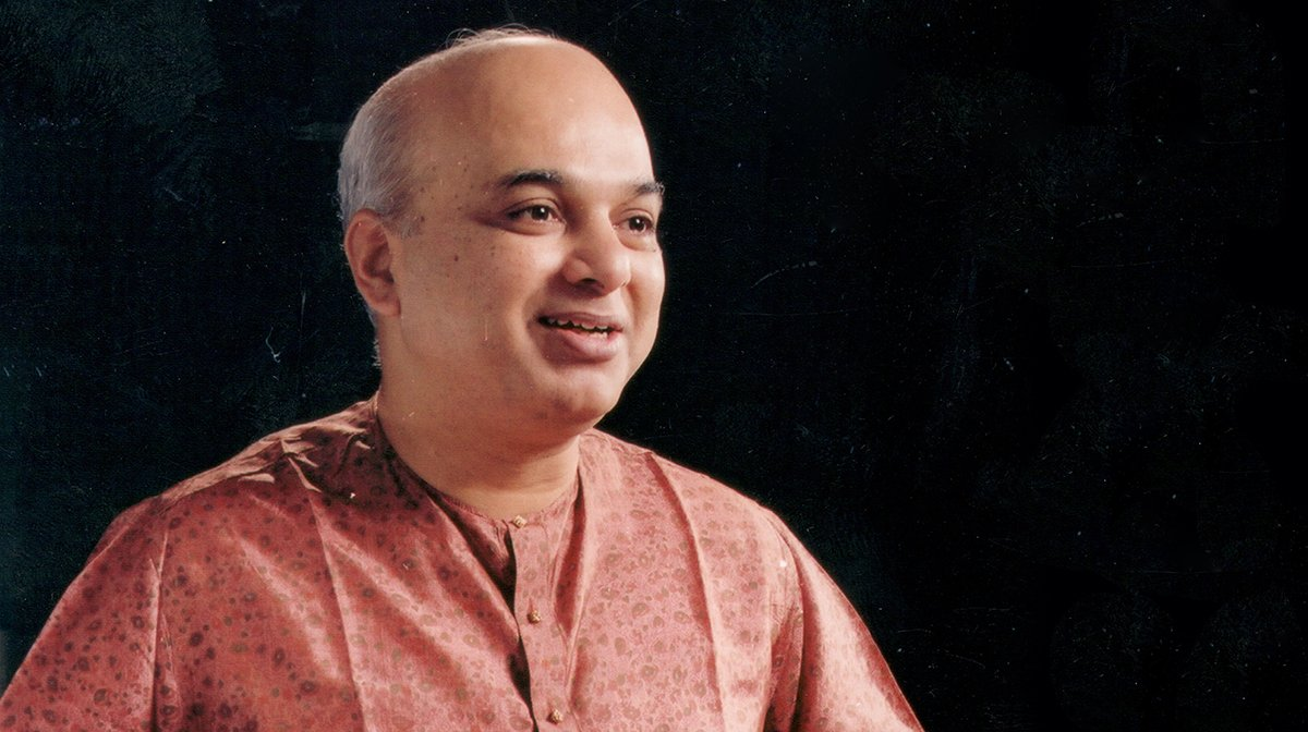 A portrait of Pandit Satish Vyas, smiling against a black background.