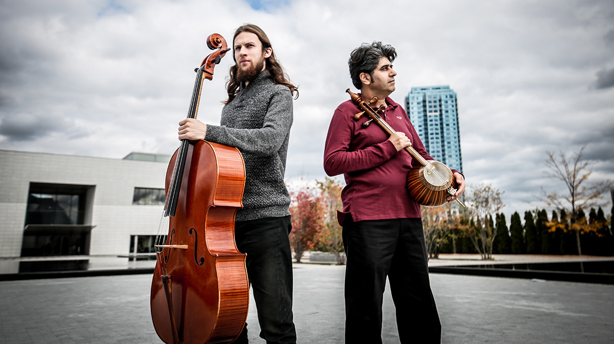 Outside the Aga Khan Museum, Raphael Weinroth-Browne stands holding a cello beside Shahriyar Jamshidi, holding a kamancheh.