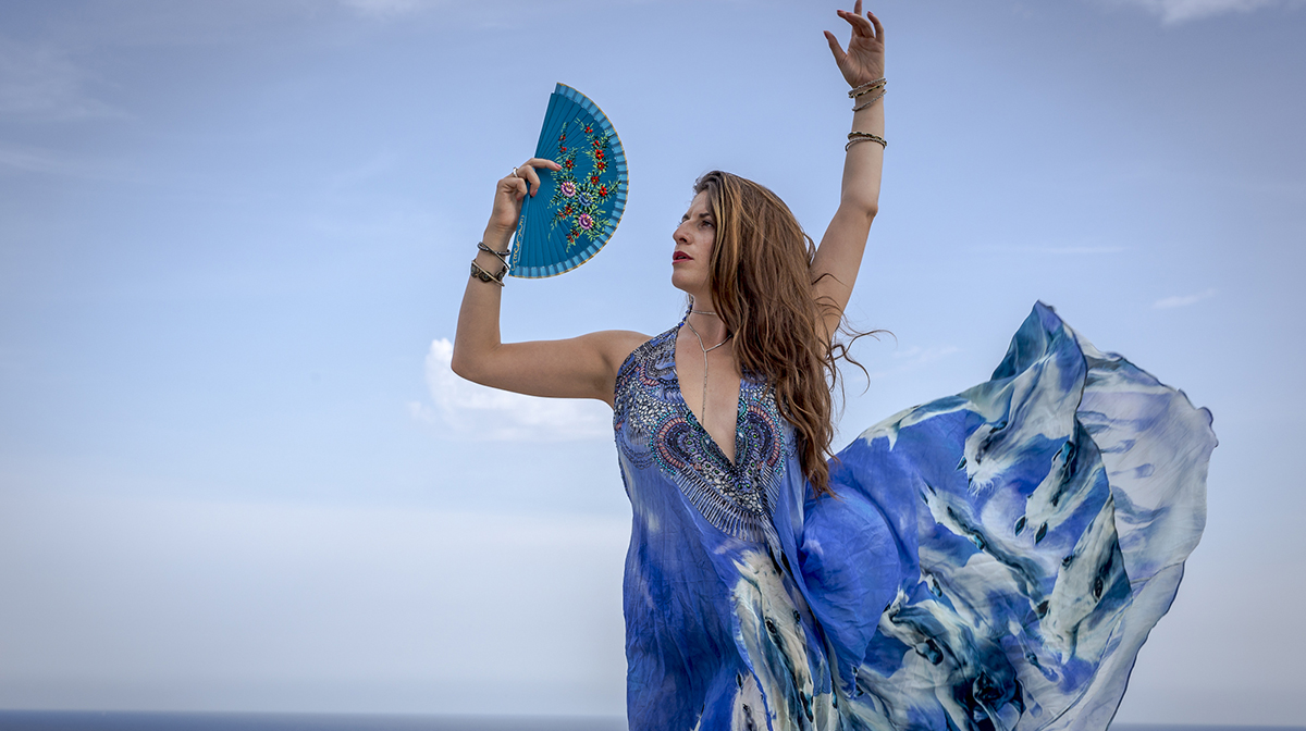 Tamar Ilana stands in a flamenco pose, holding a fan against the blue sky.