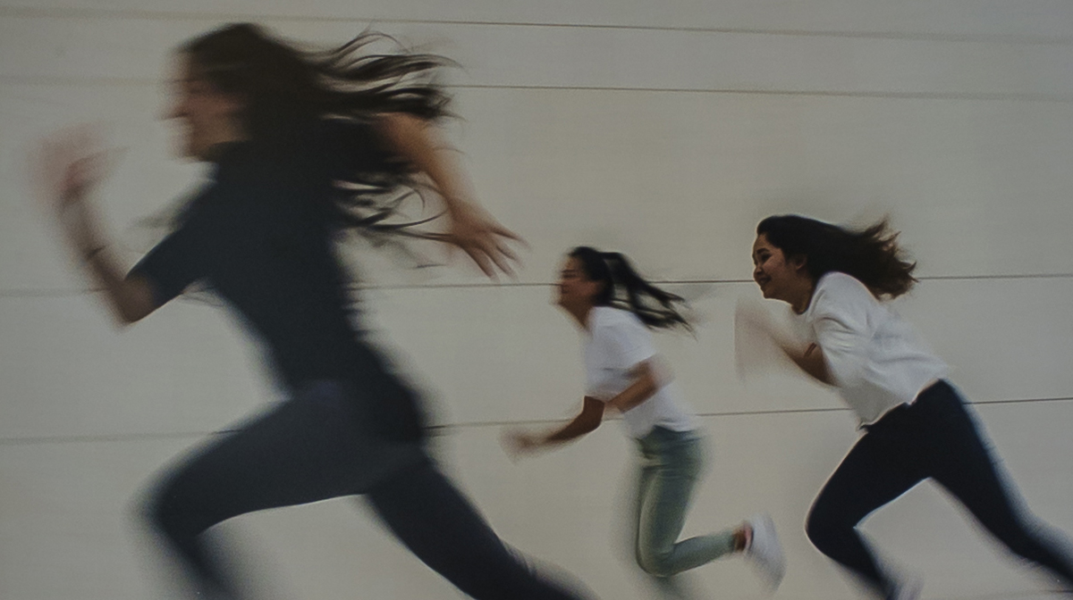 Three teenage girls, each with dark hair and a smile on her face, run in the same direction alongside a grey concrete wall.