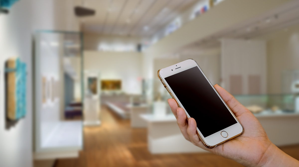 A hand holding a cell phone inside a museum gallery with glass cases and centuries-old artifacts from around the Islamic world.