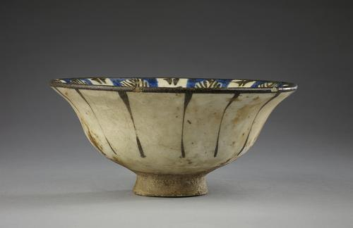 A blue, black and white-glazed pottery bowl, the white exterior with vertical black lines.