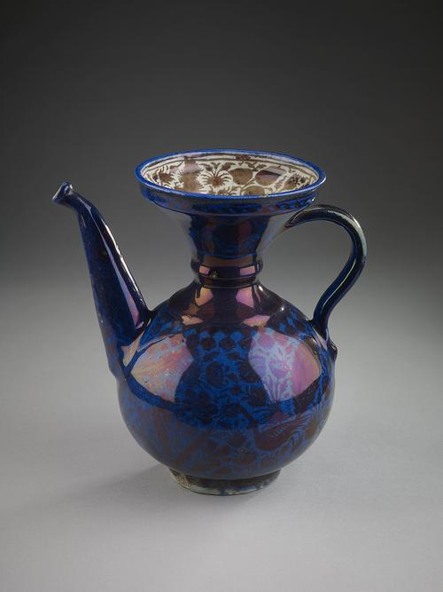 Cobalt pouring vessel with spherical body and wide flaring trumpet mouth. The interior of the flaring top is decorated with brown lustre foliate designs against a white background. On the exterior, brown peacocks and brown foliage, entire surface is covered with dark blue glaze which nearly obscures these underglaze forms.
