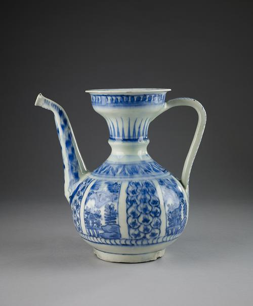 "Blue and white pitcher, wide flaring top and a bulbous body. A band of blue dots circles beneath the rim, a wider band of painted ""leaves"" circles the neck. Around the shoulder is a band of blue ""leaves"". The body is divided into eight panels."