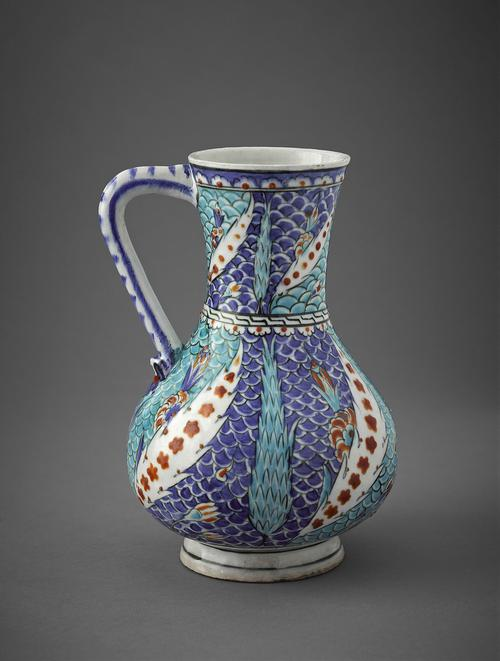 Pottery jug, the body is pear-shaped and the neck flares slightly. Around the foot is a single, blue line. The body and the neck are covered with light and dark blue scales as a background against which stand blue cypress trees, various flowers, and tilting white trees with red blossoms.