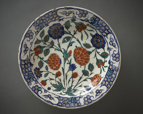 Ceramic dish, with slightly concave sides, the interior decorated with roses and buds, painted in cobalt-blue, emerald-green sealing-wax red and black against an opaque-white ground.