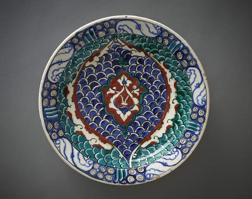 Ceramic dish with a slightly inverted rim, decorated in the centre with two long stemmed arabesque leaves forming an ogival motif and arched medallion with scalloped edges. The background decorated with a fish-scale motif in blue, green and red. The rim has scrollwork and cloud-shaped motifs.