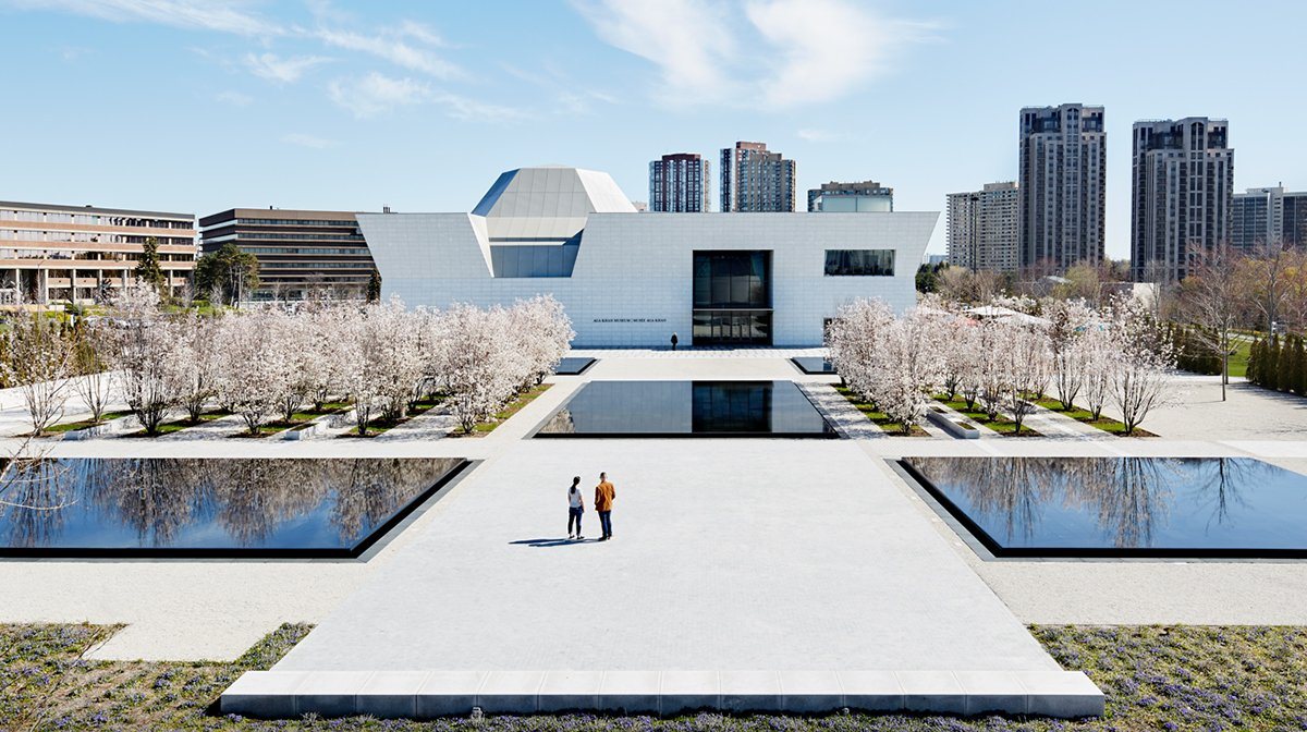 Two people stand in the middle of the Aga Khan Park in Toronto facing the west facade of the Aga Khan Museum.