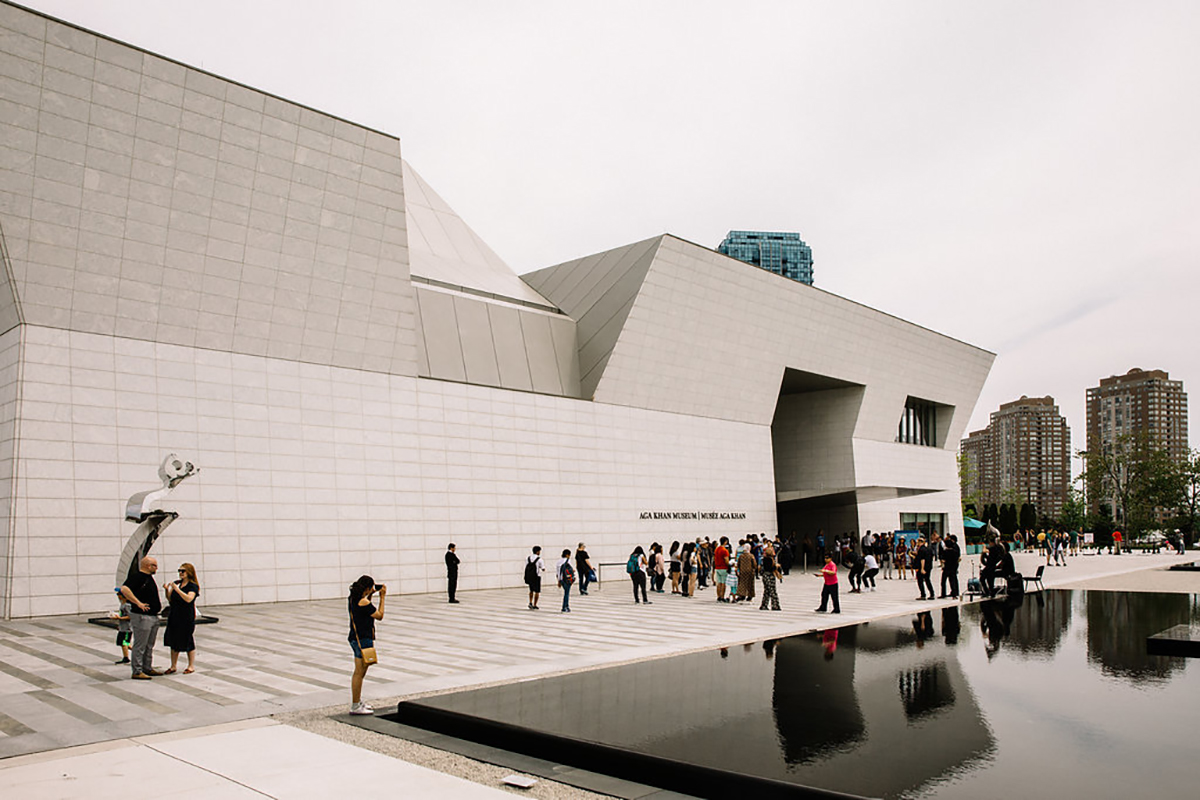Visitors stroll outside the Museum entrance and the reflecting pools in the Park
