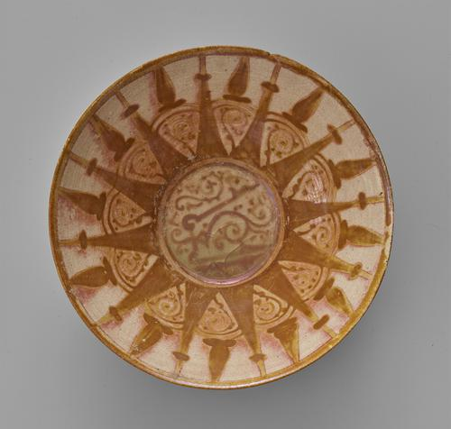 Beige bowl with brown decoration, flaring sides and slightly splayed rim, the off-white mustard glazed interior decorated with a roundel containing a kufic inscription against vines and arabesques, the roundel within twelve sunray points, between the points a trefoil above vine volutes.
