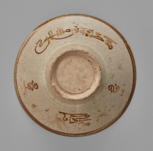 Beige bowl with a brown plain band around the rim, the exterior with a band of kufic and scrolling floral motif.