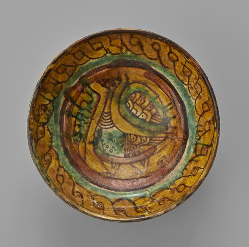 Bowl of rounded form painted in polychrome under a transparent lead-based glaze, the centre of the bowl decorated with a bird motif, and surrounded by a brown and green circular band, the rim with a twisted-rope intertwined pattern.
