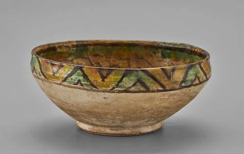 Side of bowl, beige sides with teal and yellow twisted-rop intertwined pattern along the rim.