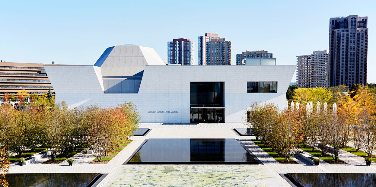 The white-Brazilian granite west-facing facade of the Aga Khan Museum in daytime.
