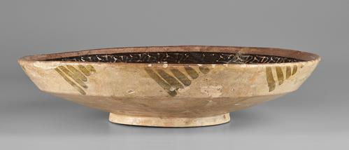 Side of shallow bowl, beige colour, outside walls decorated with repetative diagonal green lines creating a trianular shape