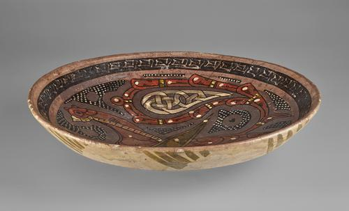 side view of bowl of shallow form, decorated in manganese-brown, tomato-red, white and olive-green slip on a purple ground with the figure of a fabulous bird with palmette wing and calligraphic band around the rim.
