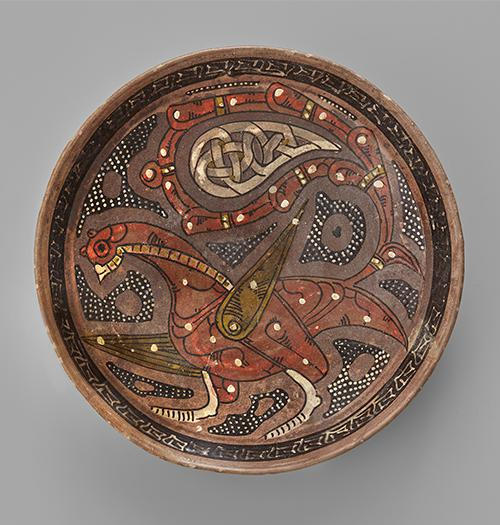 Bowl of shallow form, decorated in manganese-brown, tomato-red, white and olive-green slip on a purple ground with the figure of a fabulous bird with palmette wing and arabesque tail, a calligraphic band around the rim.