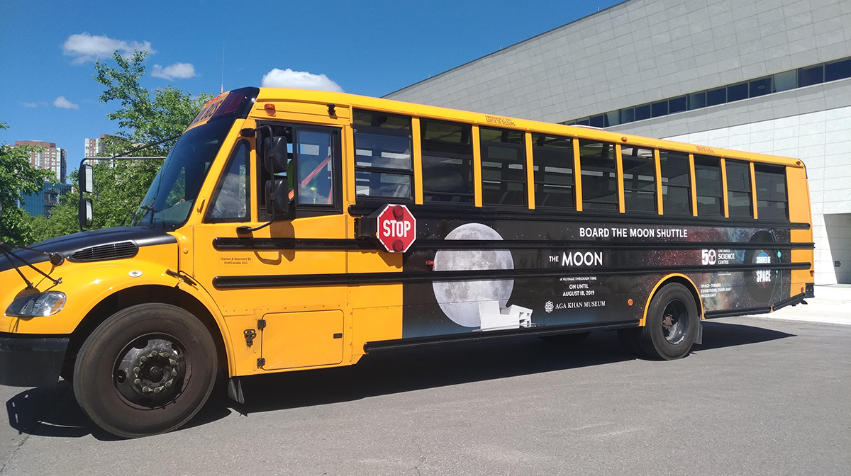 A yellow bus is parked outside in front of the Museum with a Moon shuttle banner on it.