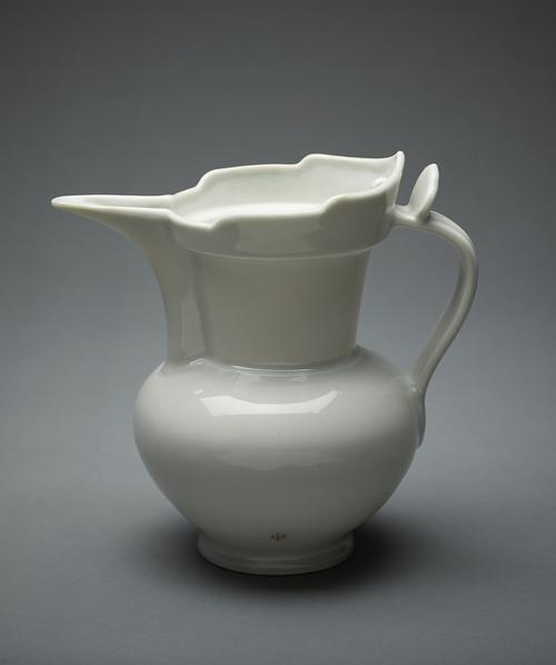 White ceramic jug, with a globular body rising from a splayed foot to a flared cylindrical neck, with a galleried monk's cap rim with a small lug on the interior, the tall spout of semi-circular section extending the full length of the neck.