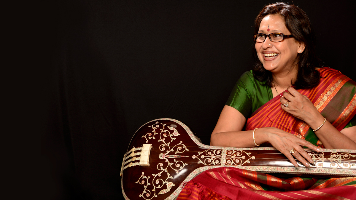 Arati Ankalikar-Tikekar sits smiling while holding a sitar and wearing a green and red outfit and glasses against a black background.