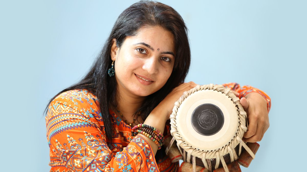 Mukta Raste, wearing an orange top and multicolored bracelet holds a tabla drum against a blue backdrop.