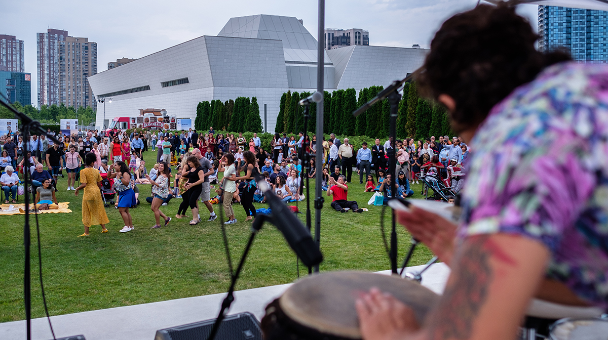 A group of people dancing outside in the background with a drummer in the foreground.