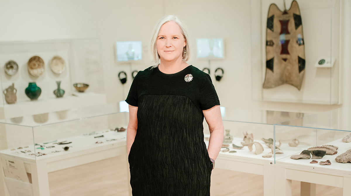 Kathleen Bickford Berzock, wearing black, stands in the exhibition Caravans of Gold.