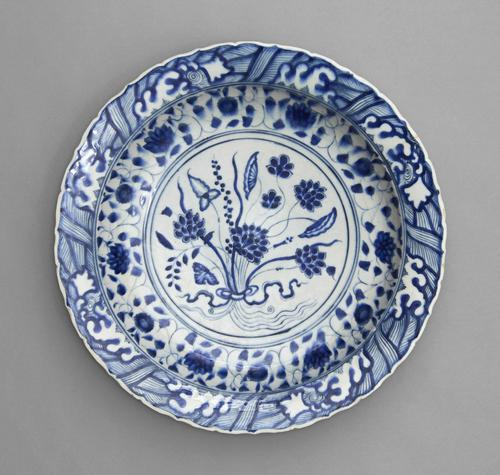 Dish follows a Chinese model so closely that it might have passed for a Chinese original if the body had been translucent like porcelain. Blue and white designs cover the white plate with a foliage design in the centre.