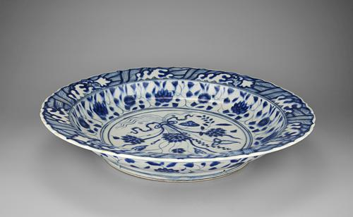 Side view of the blue and white dish that follows a Chinese model so closely that it might have passed for a Chinese original if the body had been translucent like porcelain. Blue and white designs cover the white plate with a foliage design in the centre.