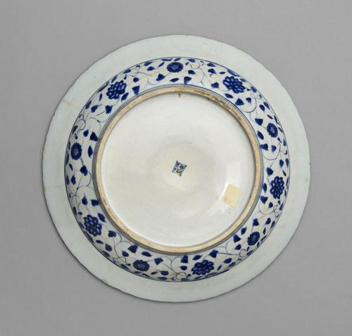 Bottom view of the dish, with blue and white designs cover the sides of the bowl, while the base and bottom of the rim are white.