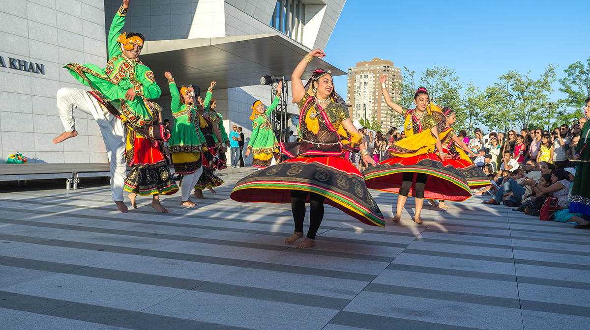 A group of large colourfully dressed dancers performing in front of the Museum.
