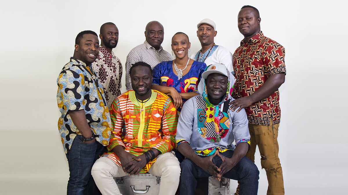 A portrait of seven men and one woman dressed in traditional African prints.