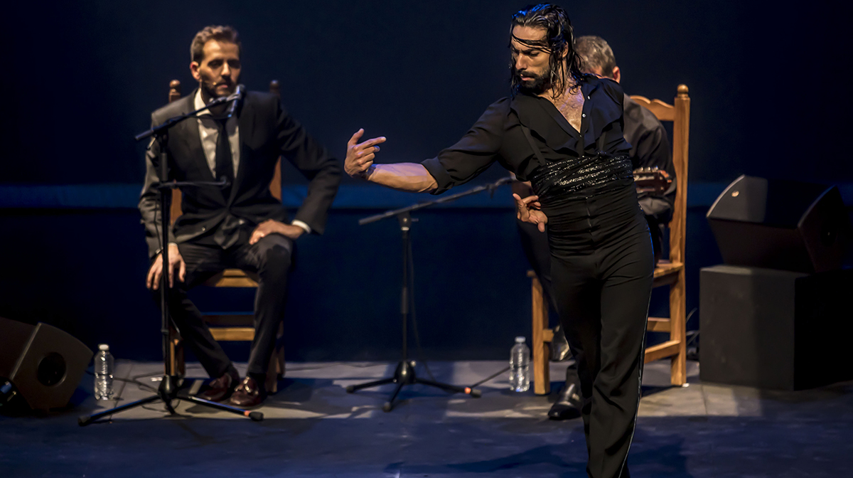Eduardo Guerreo, all in black, dances furiously on stage with a vocalist sitting in the background