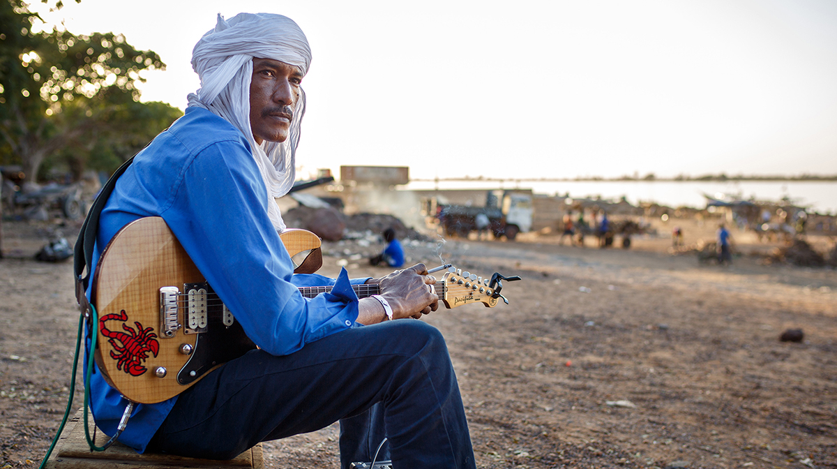 Ahmed Ag Kaedy sits on a beach, wearing a white head cover, while holding his electric guitar.