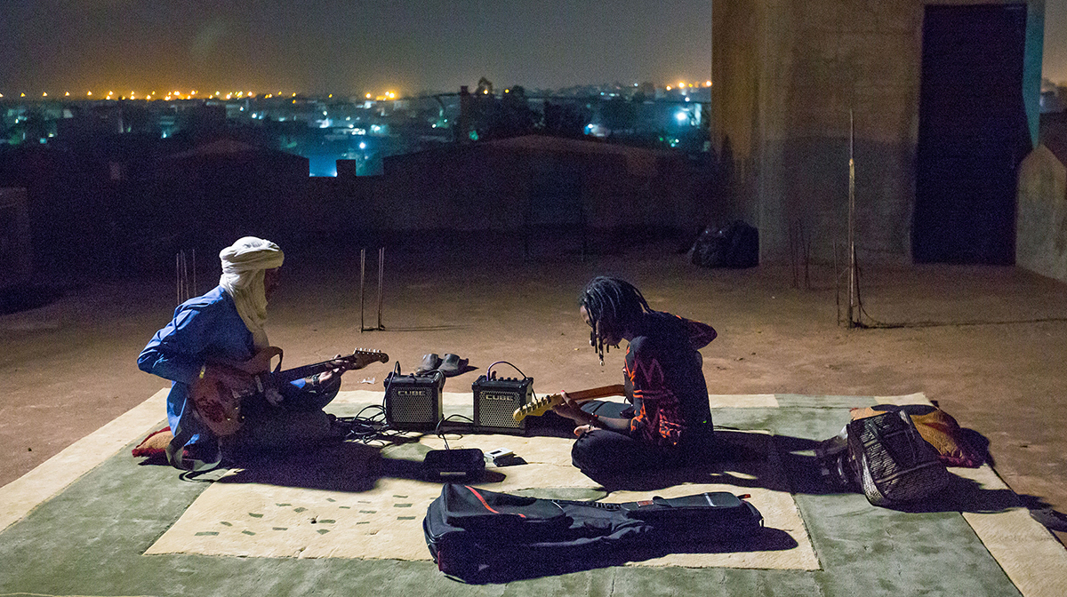 Ahmed Ag Kaedy sits on a rooftop with another guitarist at night, playing electric guitar.