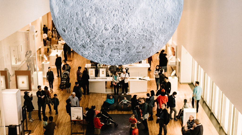 A crowd of people gather in the Museum's permanent collection gallery under the moon.