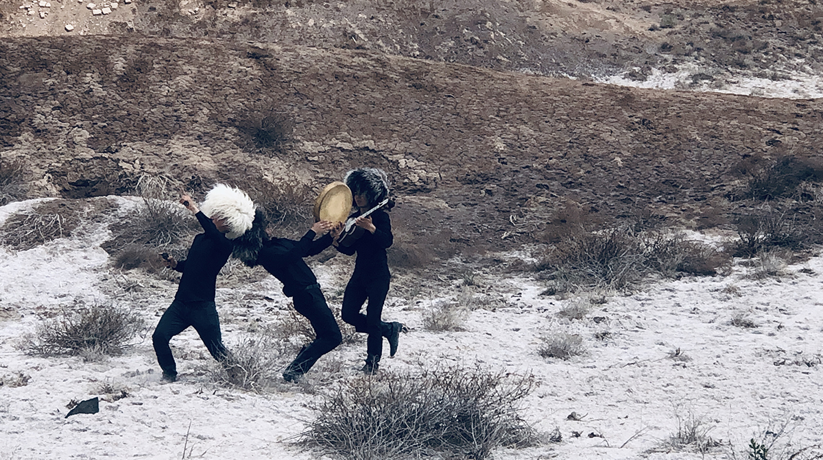 Three performers dressed in black, wearing shaggy black and white wigs, play instruments outside on scrubland.