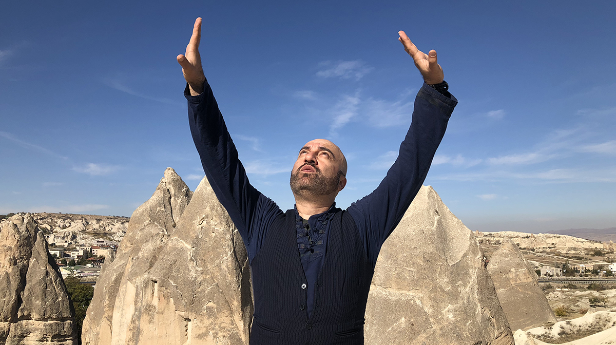 A male performer with arms raised stands outside under a blue sky in front of dramatic rocky peaks.