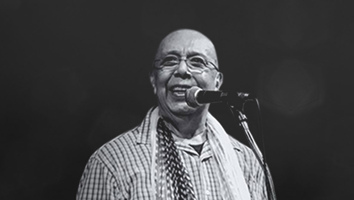 A man with a shaved head, glasses, a checkered shirt, and a scarf speaks into a microphone.