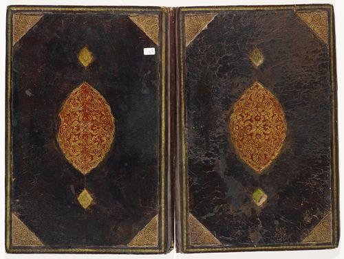 Dark brown leather bookbinding laid flat, both sides are mirror images. Golden spiral border, with gold gilt embossed triangular decorative elements on inner corners. Large golden medallion in the centre inlaid with red floral patterns. Spine of the binding has a slight rip.