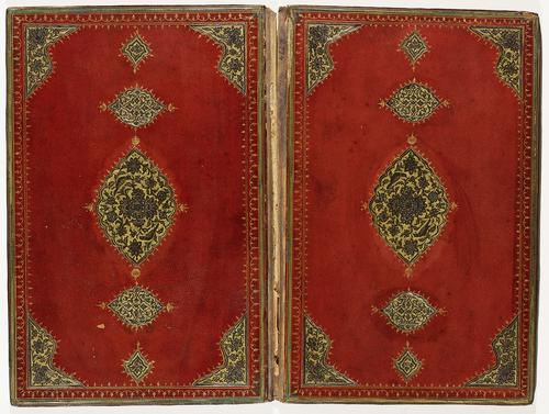 Red leather interior of bookbinding. Delicate golden border with cut-out leather flowers in black on gilt background in the corners. Large central medallion in black on gilt background and pendants in filigree.