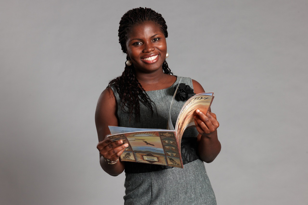 Deborah Ahenkorah smiles at the camera while holding a book open.